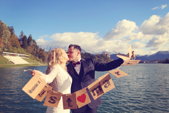 Bride and groom playing with Just Married cards - Stock Photo - Images