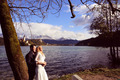 Bride and groom embracing near lake