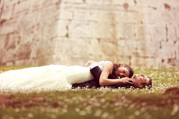 Bride and groom laying on grass - Stock Photo - Images