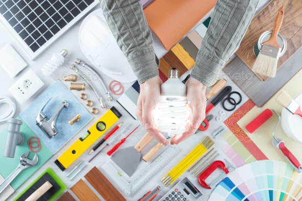 Man holding a CFL energy saving lamp - Stock Photo - Images