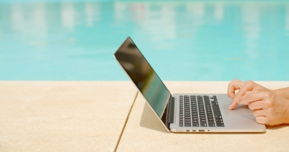 Working On Laptop In Swimming Pool Area By Daniel Dash