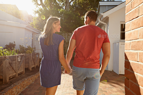 Young couple taking a walk in their backyard - Stock Photo - Images