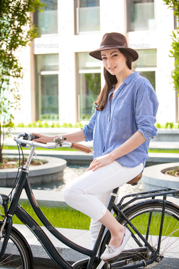 Pretty girl in hat riding a bicycle at street - Stock Photo - Images