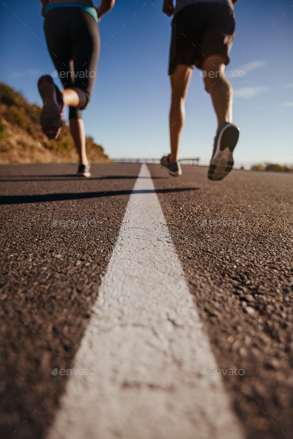 Athletes running on country road - Stock Photo - Images
