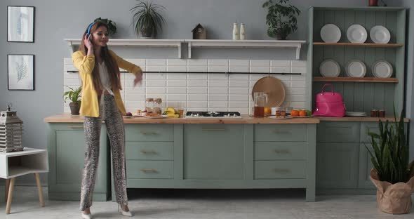 Happy Young Girl in Fashionable Clothes Dancing at Kitchen