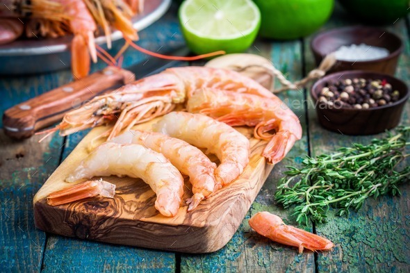 peeled raw shrimps on a wooden cutting board with salt, pepper, lime - Stock Photo - Images