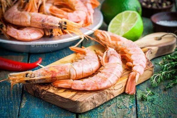 fresh raw prawns on a wooden cutting board with salt, pepper, lime - Stock Photo - Images