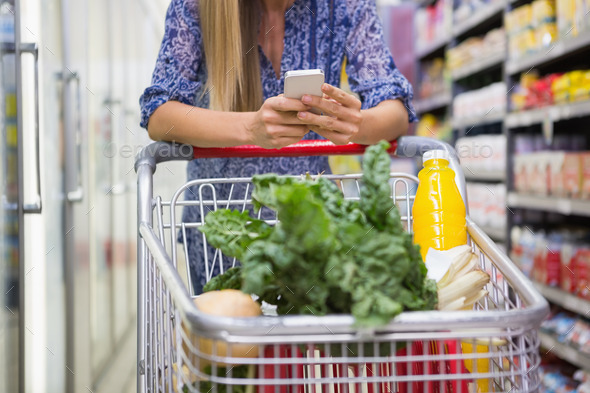 Woman buy products and using his smartphone  at supermarket - Stock Photo - Images