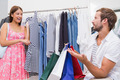Smiling woman showing clothes to her man at a boutique