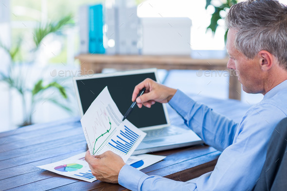 Businessman looking at documents with graphic in office - Stock Photo - Images