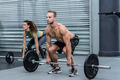 Muscular couple lifting weight together at the crossfit gym - PhotoDune Item for Sale
