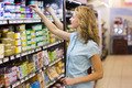 Pretty blonde woman taking a products in shelves in supermarket - PhotoDune Item for Sale
