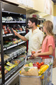 Smiling bright couple buying food products at supermarket - PhotoDune Item for Sale