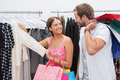 Smiling couple with shopping bags looking at clothes at a boutique
