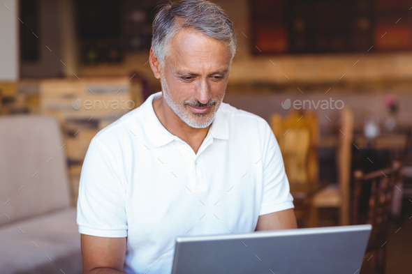 Happy man using his laptop computer - Stock Photo - Images