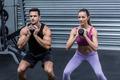 Kneeling muscular couple exercising with kettlebells