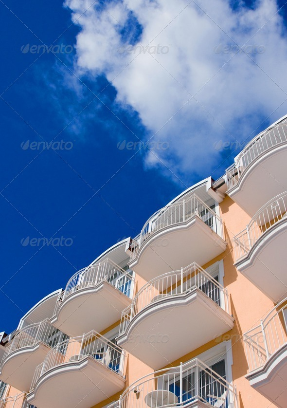 Orange Hotel in front of a blue sky - Stock Photo - Images