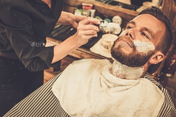 Client during beard shaving in barber shop - Stock Photo - Images