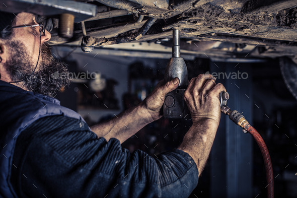 Mature mechanic at repair service station unwound screw - Stock Photo - Images