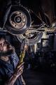 Mature mechanic at repair service station inspecting car suspen - PhotoDune Item for Sale
