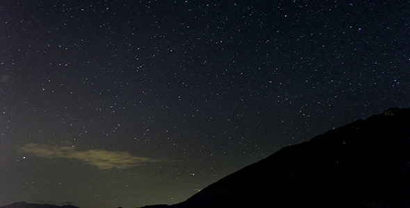 Stars Moving In Night Sky Over Mountain Ridge