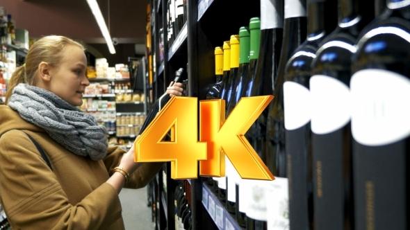 Woman In The Store Choosing Bottle Of Wine