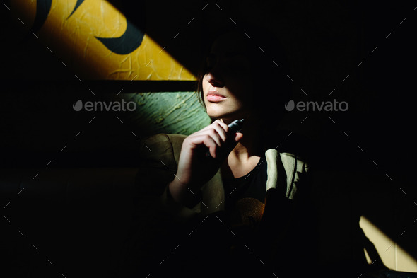 girl sits and smokes electronic cigarette - Stock Photo - Images