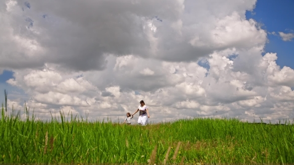 Happy Mother And Small Son Walking In Green Field