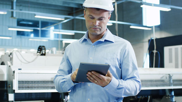 Engineer in Hard Hat is Using Tablet PC on Factory