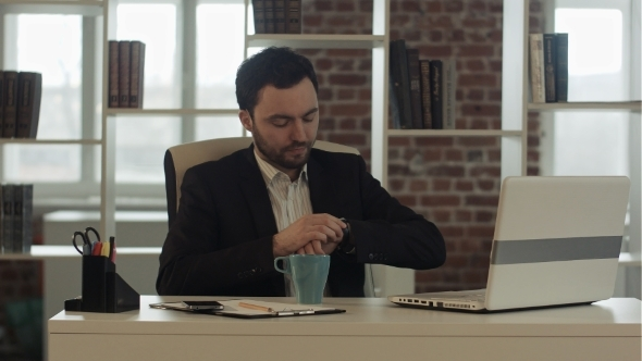 Businessman With a Laptop And Tea Looking At His