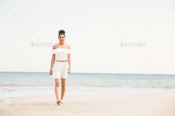 Stylish woman walking on the sand at the beach - Stock Photo - Images