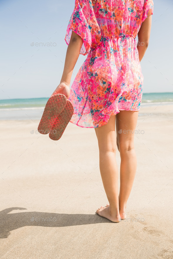 Stylish woman standing on the sand at the beach - Stock Photo - Images