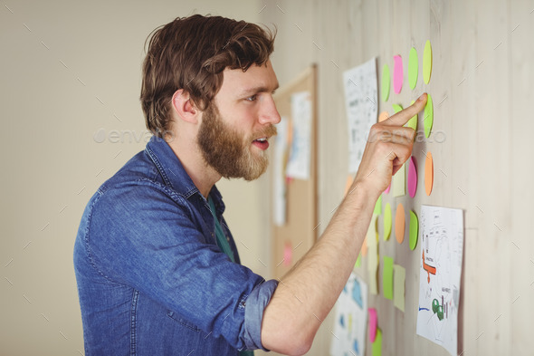 Bearded hipster looking at brainstorm wall in his office - Stock Photo - Images