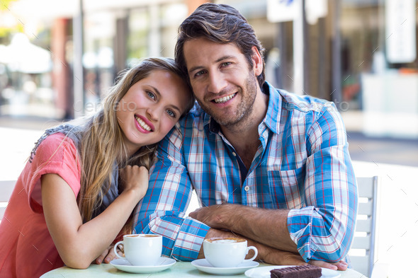 Smiling couple having tea in a cafe on a sunny day - Stock Photo - Images
