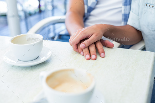 Cute couple on a date holding hands at the cafe - Stock Photo - Images