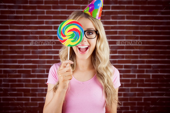 Portrait of a hipster hiding herself behind a lollipop against a brick wall - Stock Photo - Images
