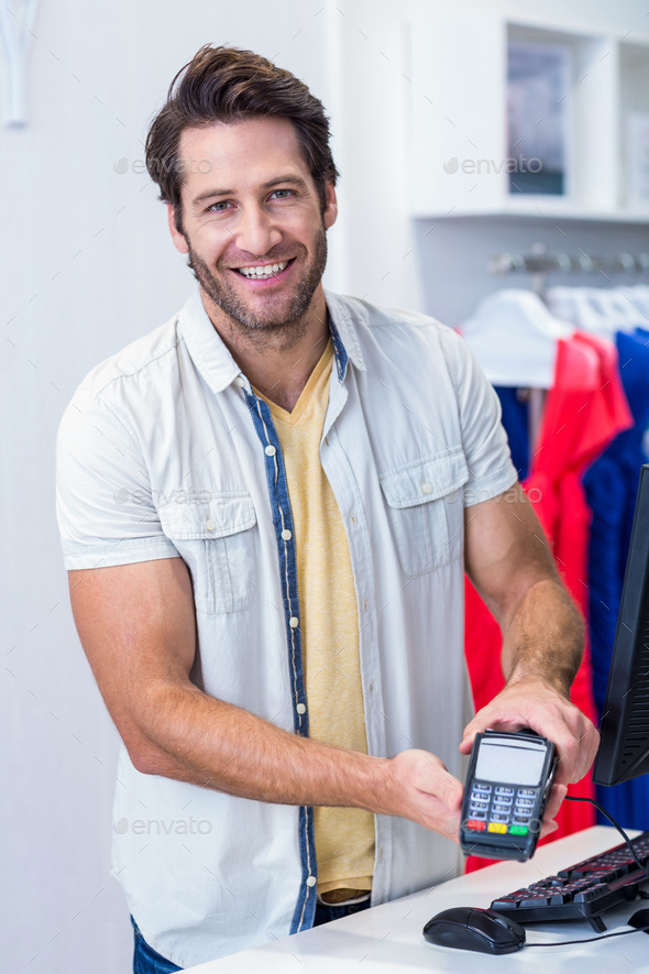Portrait of smiling cashier showing credit card reader in clothing store - Stock Photo - Images