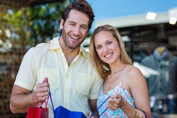 Portrait of smiling couple holding shopping bags at shopping mall - Stock Photo - Images