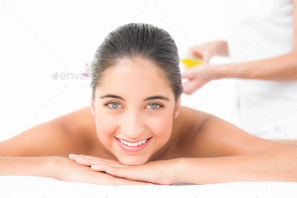 Portrait of a beautiful brunette enjoying an oil massage at the health spa - Stock Photo - Images