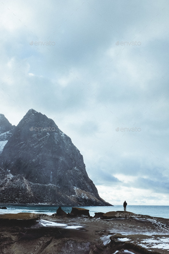 Fjord beach with man silhouetted agains the sky and sea - Stock Photo - Images