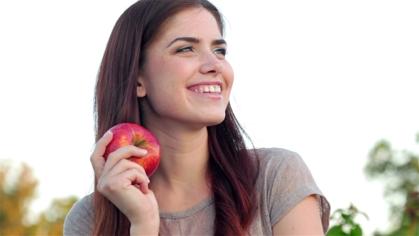 Portrait Of Smiling Beautiful Girl With An Apple