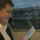 Man In Train Laughing At Tablet - VideoHive Item for Sale