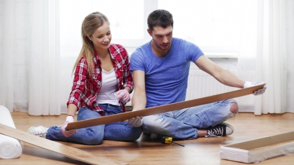 Happy Couple Measuring Wood Flooring Board At Home