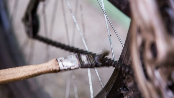 Cyclist Cleaning Bicycle Chain With Brush