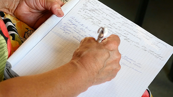 Woman Writes A Pen In A Notebook