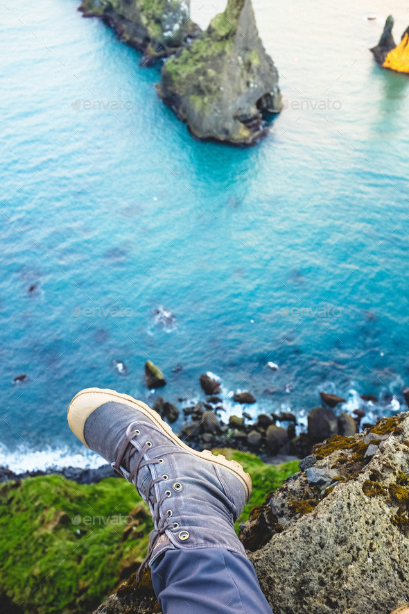 Feet dangling from ledge looking at rock formation - Stock Photo - Images