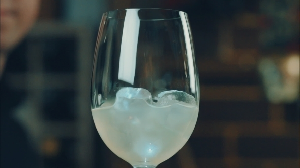 The Bartender Throws a Lemon In a Glass With Ice