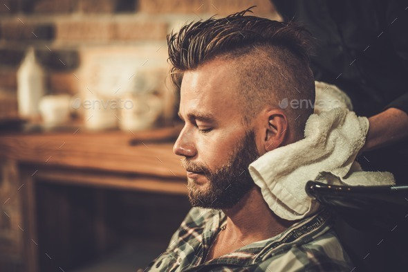 Hairstylist washing client's hair in barber shop - Stock Photo - Images