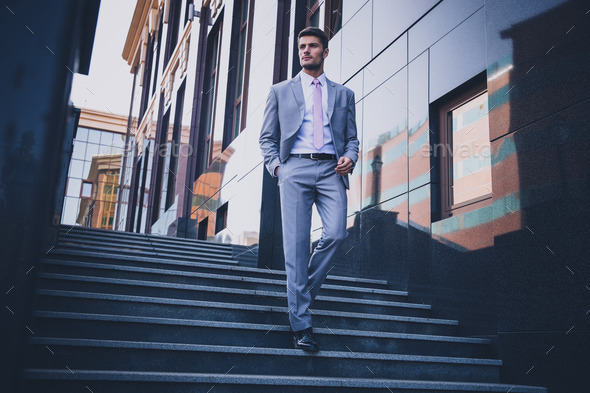 Businessman walking on the stairs outdoors - Stock Photo - Images