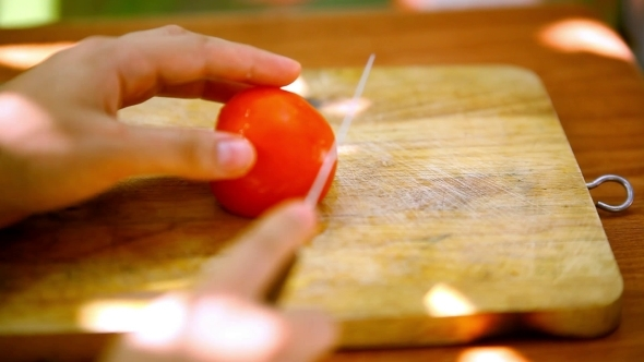Female Hands Sliced Tomato On a Wooden Board